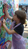 A young visitors gets hands on with  the Pershore Arts Mural at Pershore Plum Festival